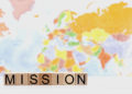Mission Spelled in Block Letters Against a Background of a World Map
